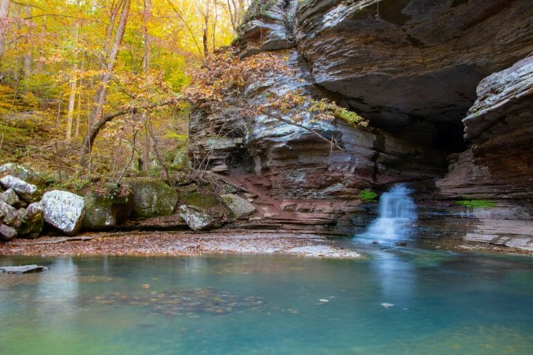 The natural bridge at Lost Valley Trail with a small stream coming out of it. Lost Valley Trail is the most beautiful and unique of the hiking trails in Arkansas.