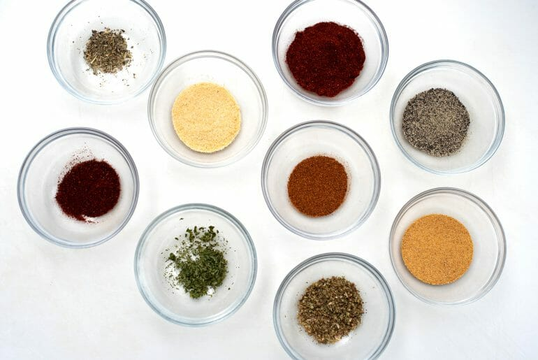 9 small clear glass pinch jars are sitting on a white background. Each jar is filled with different types of spices and herbs. The colors are greens, red, golds, and dark brown.