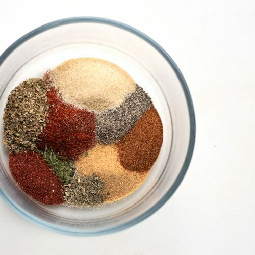 There are spices and herbs in a clear glass bowl on a white background. THe spices are all in the bowl but aren't mixed up yet. The colors are vibrant reds, browns, golds, and greens. These are spices for a salt free cajun seasoning blend.
